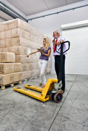 Woman & man standing next to a hand pallet truck in a warehouse